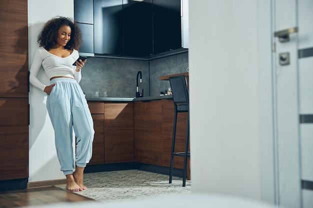 彼女の携帯電話を保持し、笑顔でキッチンの壁にもたれて美しいアフリカ系アメリカ人の女性