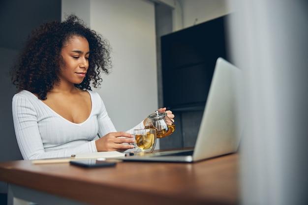 아름 다운 흑인 여성 그녀의 노트북 근처에 앉아 컵에 차를 붓는 동안 웃 고