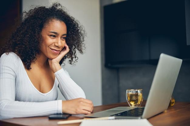 테이블에 차 한잔하는 동안 노트북에서 작업하는 아름 다운 아프리카 계 미국인 여성