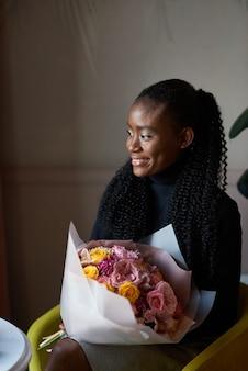 Красивая афроамериканская девушка держит букет цветов на свидании в кафе