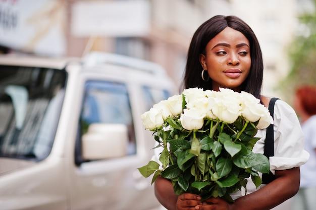 手に花を持つ白いドレスの美しいアフリカ系アメリカ人の女の子