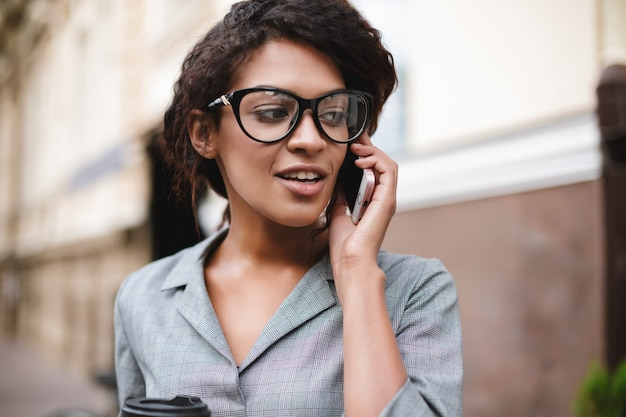 通りに立って、彼女の携帯電話で話している眼鏡の美しいアフリカ系アメリカ人の女の子