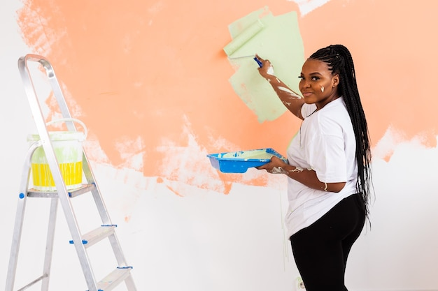 Красивая афро-американская девушка красит стену валиком. портрет молодой красивой