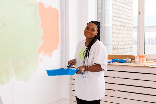 Beautiful african american girl painting the wall with paint roller. portrait of a young beautiful
