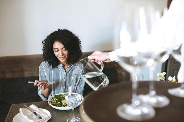 웨이터가 유리에 물을 붓는 동안 레스토랑에 앉아 샐러드를 먹는 아름다운 아프리카 계 미국인 여자