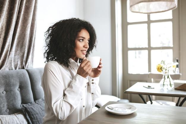 手にカップを持ってレストランに座っている美しいアフリカ系アメリカ人の女の子。カフェでコーヒーを飲む白いシャツの若いきれいな女性