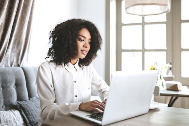 ノートパソコンとレストランに座っている美しいアフリカ系アメリカ人の女の子。カフェで自分のコンピューターで作業しているかわいい女の子