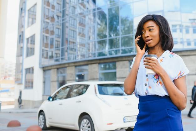 喜んでよそ見しながら携帯電話とコーヒーを手に路上に立っている美しいアフリカ系アメリカ人の女の子。