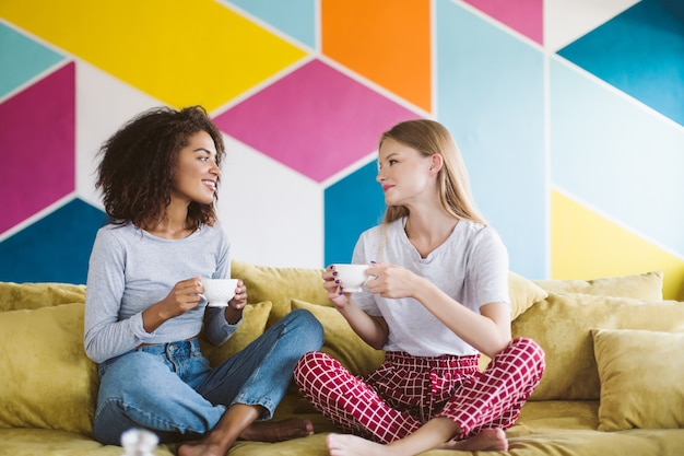 Красивая афроамериканская девушка с темными вьющимися волосами и красивая девушка со светлыми волосами сидит на диване, держа в руках чашки кофе, мечтательно разговаривая с красочной стеной