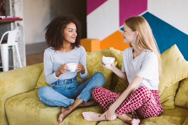 Красивая афро-американская девушка с темными вьющимися волосами и красивая девушка со светлыми волосами, сидя на диване, держа в руках чашки кофе, счастливо проводя время вместе дома