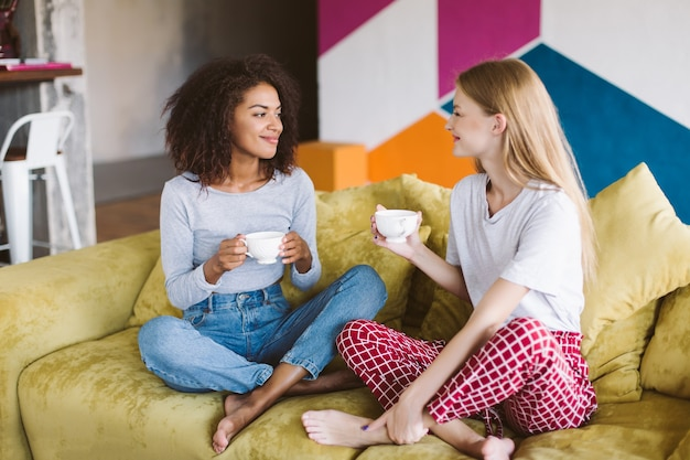 Beautiful african american girl with dark curly hair and pretty girl with blond hair sitting on sofa holding cups of coffee in hands while happily spending time together at home