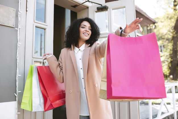 Beautiful african american girl with dark curly hair standing with shopping bags in her hands. young smiling lady with packets catching taxi