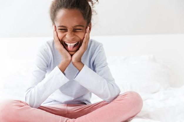 Красивая афро-американская маленькая девочка улыбается, сидя в постели у себя дома