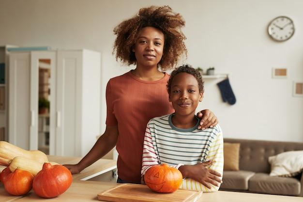 아름 다운 아프리카 계 미국인 여자와 그것에 조각에 대 한 호박 테이블에 함께 서있는 그녀의 십 대 아들
