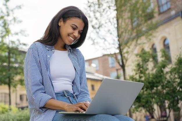 働くフリーランスプロジェクトを入力する美しいアフリカ系アメリカ人女性のコピーライター
