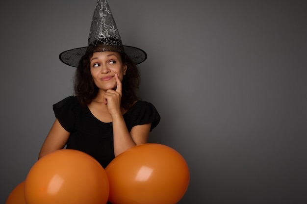 黒と魔女の帽子に身を包んだ美しいアフリカ系アメリカ人の女性は、オレンジ色の気球をのぞき、灰色の背景に広告のコピースペースの横に思慮深く見えます。ハッピーハロウィンコンセプト