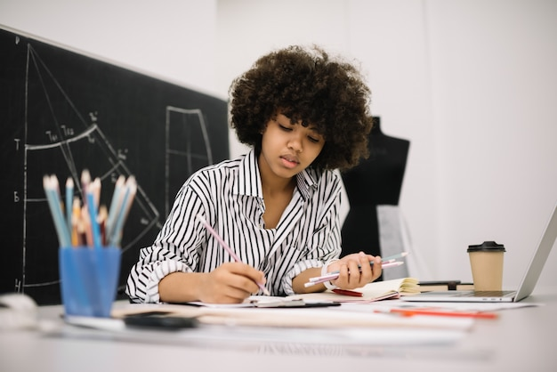 Beautiful african american woman freelancer sketching or drawing at workplace