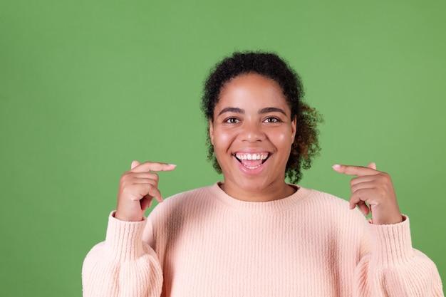 Bella donna afroamericana sulla parete verde allegro sorridente punto di indice sui denti bianchi sorriso