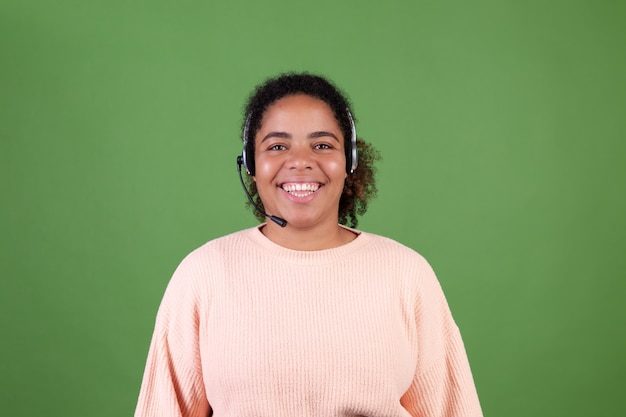 Beautiful african american woman on green wall manager call centre worker happy adorable smiling welcoming all calls