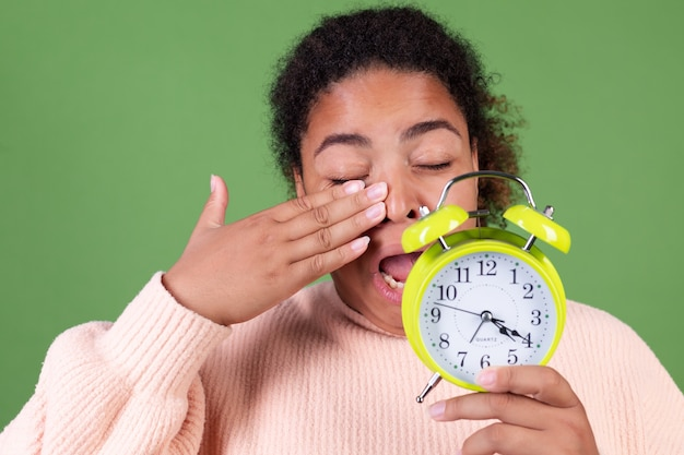 Beautiful african american woman on green wall with alarm clock sleepy tired exhausted yawning