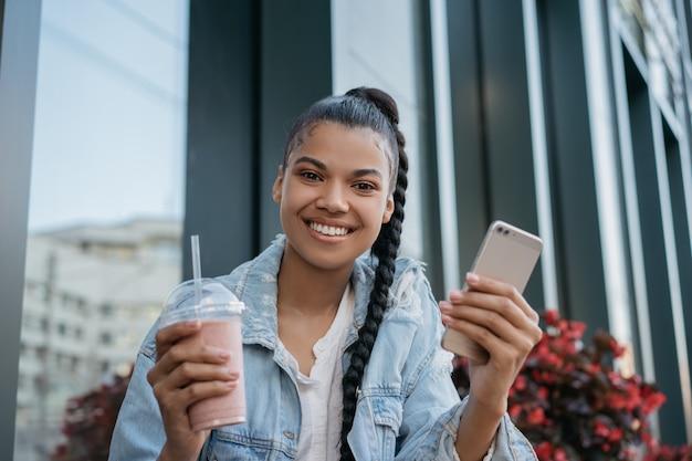 Красивая афроамериканская женщина, держащая стакан с коктейлем и смартфоном
