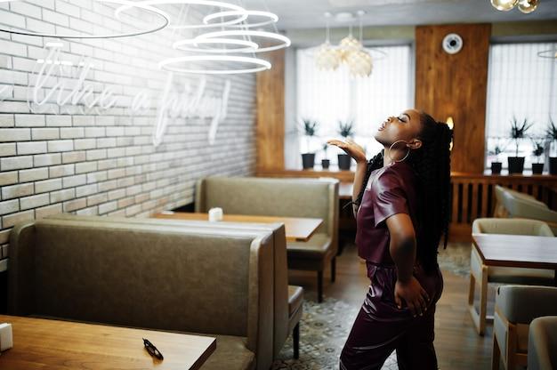 赤い革の衣装を着た美しいアフリカ系アメリカ人女性がレストランでポーズをとる。