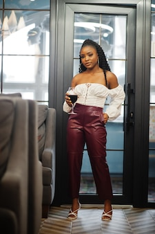 Красивая афро-американская женщина в белой блузке и красных кожаных штанах позирует в ресторане с бокалом вина.