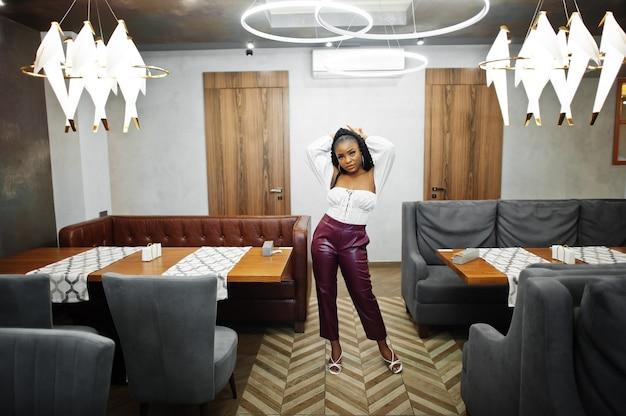 Красивая афро-американская женщина в белой блузке и красных кожаных штанах позирует в ресторане.
