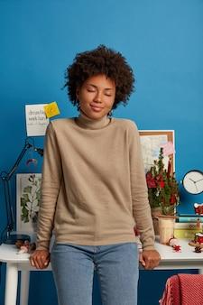 美しいアフリカ系アメリカ人の女性はデスクトップに寄りかかって、目を閉じて職場に立ち、茶色のカジュアルなジャンパーとジーンズを着ています
