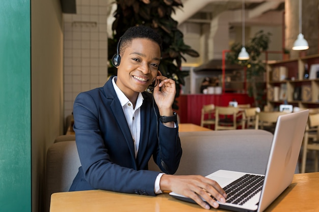 Beautiful african american woman looking at camera and smiling, working in coworking cafe, video communication using headset business woman freelancer