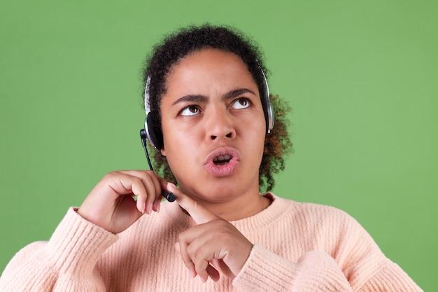 緑の壁のマネージャーのコールセンターの労働者がマイクをチェックしている美しいアフリカ系アメリカ人の女性