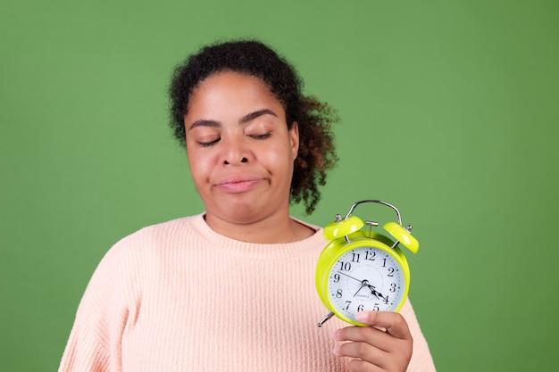 目覚まし時計で緑の壁に美しいアフリカ系アメリカ人の女性怒って疲れて不幸