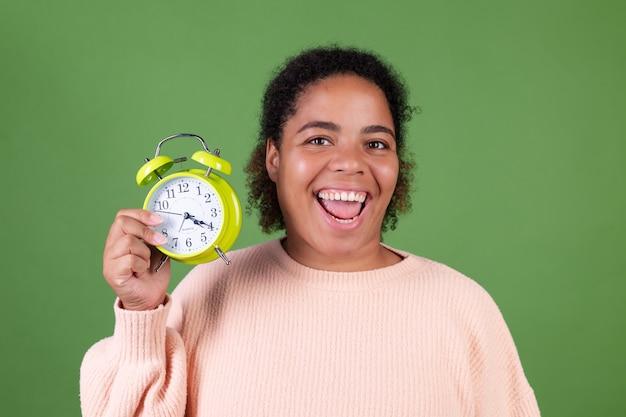 Красивая афро-американская женщина на зеленой стене с будильником счастливый улыбающийся веселый