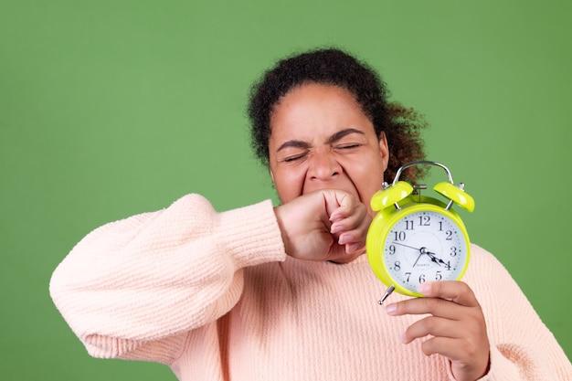 目覚まし時計と緑の壁に美しいアフリカ系アメリカ人の女性眠い疲れた疲れたあくび