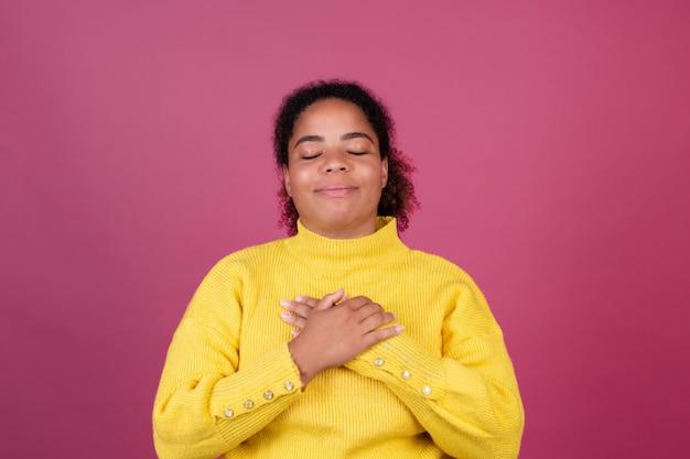 Красивая афро-американская женщина на розовой стене, счастливые улыбающиеся руки на груди, концепция любви, самообслуживания