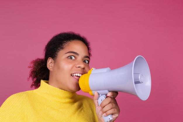 メガホンで叫んでいるピンクの壁に美しいアフリカ系アメリカ人の女性が注意を求めます