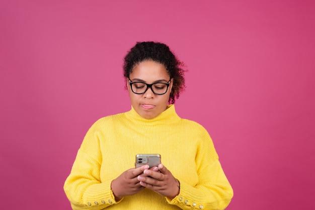 분홍색 벽에 있는 아름다운 아프리카계 미국인 여성이 휴대전화에 메시지를 입력하며 사려깊은 데 초점을 맞췄습니다.