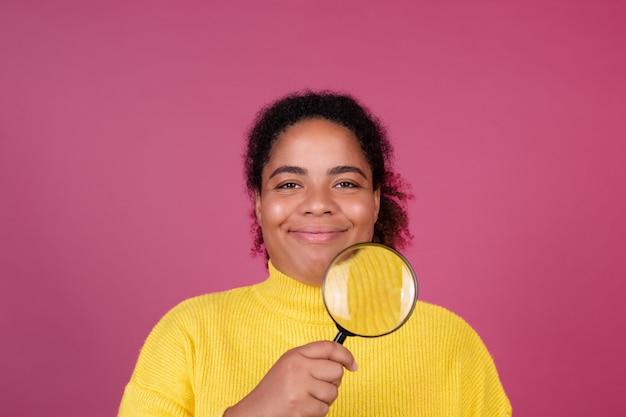 La bella donna afroamericana sulla parete rosa con il sorriso della lente d'ingrandimento e guarda alla macchina fotografica