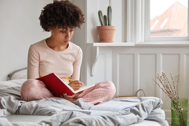 Bella donna afroamericana si siede sul letto, incrocia le gambe, prende appunti al diario tiene la penna in mano