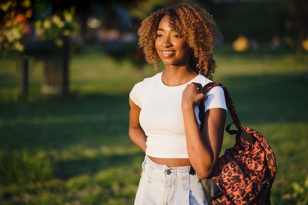 アフリカ系アメリカ人の美人笑顔と離れて公園を見てします。