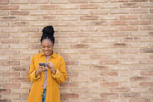 벽 복사 공간 근처에 서서 온라인 쇼핑을 하는 아름다운 아프리카계 미국인 여성