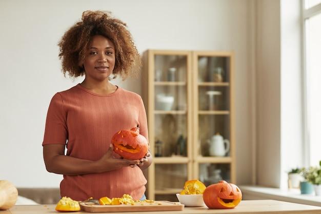 할로윈에 새겨진 호박을 들고 식탁에 서 캐주얼 복장을 입고 아름 다운 아프리카 계 미국인 여자