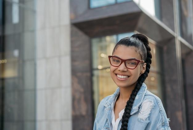 Красивая афро-американская женщина в стильных очках, стоя на улице