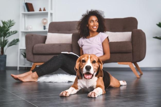 かわいい犬を家にいる美しいアフリカ系アメリカ人女性