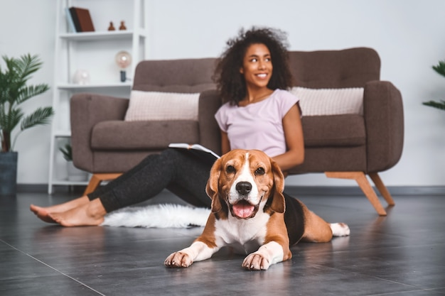 Beautiful african-american woman with cute dog at home