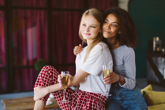 Beautiful african american woman with dark curly hair and pretty woman with blond hair leaning on each other with glasses of champagne in hands while dreamily looking aside at home