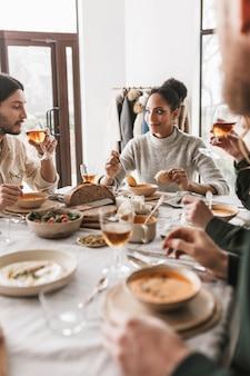 꿈꾸는 빵 조각으로 수프를 먹는 테이블에 앉아 검은 곱슬 머리를 가진 아름 다운 아프리카 계 미국인 여자