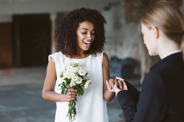 Beautiful african american woman with dark curly hair in white dress holding little bouquet of flowers in hand while happily on wedding ring