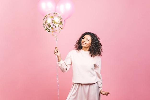 カラフルなパーティー風船とピンクのtシャツと美しいアフリカ系アメリカ人の女性