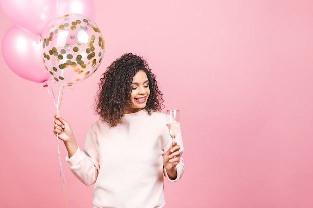 Beautiful african american woman with pink t-shirt with colorful party balloons